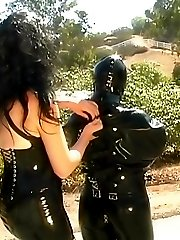 Domina in latex dress trains a submissive woman whipping her outdoors