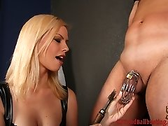 Tara Lynn has a slave bound to a cross and his cock and balls locked in a steel chastity device....