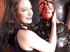 Two merciless mistresses keep their latex slave in bondage and train him