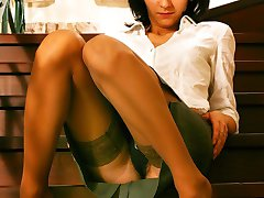 Upskirts amateur in beige stockings sits on the stairs