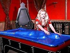 Fetish nurse Nicolette puts her cute slave under a latex cover