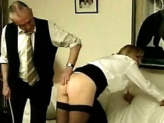 He spots his paddle and bends her over, punishing her bottom with a good paddling. She isn't flinching enough, so he takes out his thin cane, leaving a few strikes against her skin.