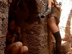 Fetish lesbo mistress in latex cat mask makes her sexy slave hide in a niche and climb the wall