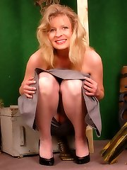 Blonde military girl in grey colored stockings and long dress