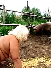 Fat babe gets down and dirty sucking cock in the mud with pigs
