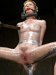 Jeze is locked into stocks. Her neck and wrists in one and her ankles in another. The platform she stands on is adjustable, and it can lower to stretch her out or raise and put her in a brutal squat. She is tantalized and then allowed to ejaculation.Next she is belted on the floor with her feet pulled up and locked in cold steel. Her soles are tormented to her cracking point. She is adorned in hot paraffin wax and then made to fight through the anguish she has suffered and orgasm. In the final scene she is bound and packaged in plastic in a sitting pose. She is tortured more and her final ejaculations are mind arching.