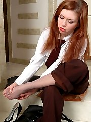 Red hot business woman in grey pantyhose caressing her feet on the floor