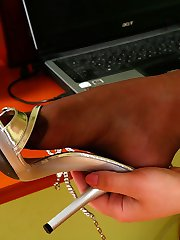 Blonde secretary putting to work her feet encased in reinforced toe hose