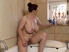 Well stacked brunette milf faux-cock screws her cleavage in the bath room