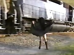 Asian girl in trench coat demonstrates train