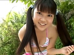 Nice Korean college student poses in swimsuit in the garden