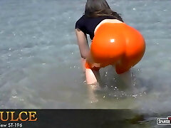 Big bottomed teen bathes her cameltoe at the beach
