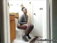 Dark-hued  girl pooping on the toilet