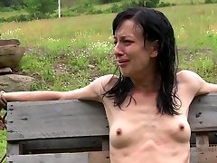 Anorexic dark haired hussy gets her slim body tied up to wooden fence outdoors