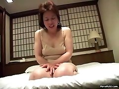 Asian grandmother inserts a vibrator in her pussy