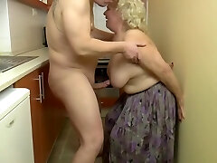Insatiable, blonde granny is playing with her mammories and her lovers dick, in the kitchen