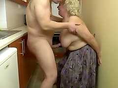 Insatiable, light-haired granny is playing with her udders and her lovers dick, in the kitchen