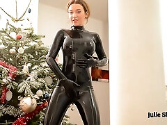 Kinky redhead in a taut black latex costume rubs her raw pussy on the floor while moaning