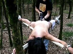 Tied to a cross and fucked with a big fake penis in the woods