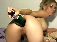 Crazy blondie uses the ample end of a bottle to stick in her arse