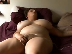 plumper girl with glass jacks on bed