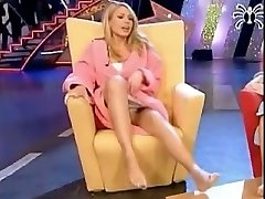 A sexy blonde woman shows off her soles in a TV show