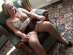 Attractive busty granny in stockings undressing