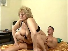 A blonde gran with glasses rides her red-hot young man