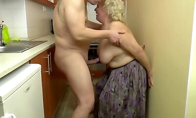 Insatiable, blonde granny is playing with her tits and her paramours prick, in the kitchen