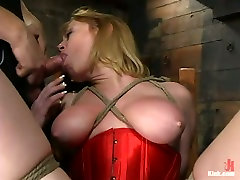 Busty whore in red corset is tied up and throated in bdsm room