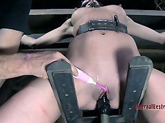 Well shaped black haired babe Elise Graves spins on extreme shoes worship slave wheel