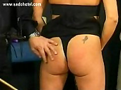 Older slave sitting in a chair is spanked on her bald pussy by master bdsm