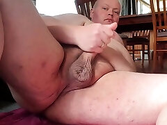 Fat man masturbates close up.