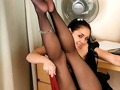 Mischievous girl spreads her long legs while showcasing her nyloned feet