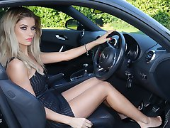 Gorgeous leggy blonde Kathryn is behind the wheel of a powerful Audi sport car, in tall black shiny pair of stiletto heels