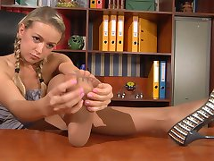 Foxy secretary dangles her shoe and massages her tired nyloned feet at work