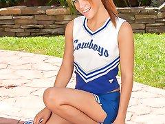 Naughty cheerleader Daisy Dalton gets naked outdoors.