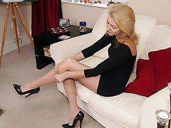 Blonde Milf Magdalena shows off her long legs in a pair of silky nylon stockings and tall black...