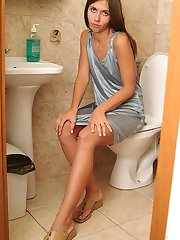 Horny brunette frigging her fanny in the toilet!