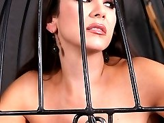 Jewell Marceau is locked in a cage and suspended off the ground. With nothing else to do, she spends her time getting herself off with a vibrator.