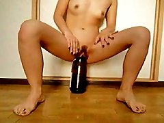 Young Asian slut fucking her huge cunt with a wine bottle
