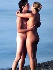 Naturist couple sunbathing and cuddling