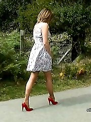 Sexy and seductive Carrie gives you a leggy walk in red patent leather heels and a short dress