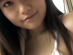 Busty Japanese hottie demonstrates her charms in white bikini