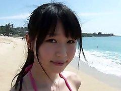 סלים בחורה אסייתית Tsukasa אראי הולך על חוף חולי תחת השמש