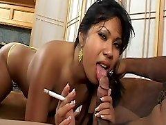 Āzijas medus ar jaukām krūtīm smēķē cigareti un saņem cum sejas uz dīvāna