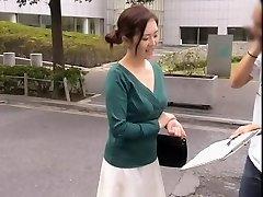 Vriendelijke Aziatische gal blijft glimlachen terwijl haar decolleté is volledig onthuld