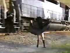 Asiatisk jente i trenchcoat blinker tog