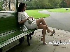 Ganske jente viser henne silkeaktig glatt nylon ben og posh høye hæler