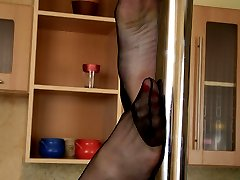 Sultry chick in black pantyhose getting down to pleasure giving foot games